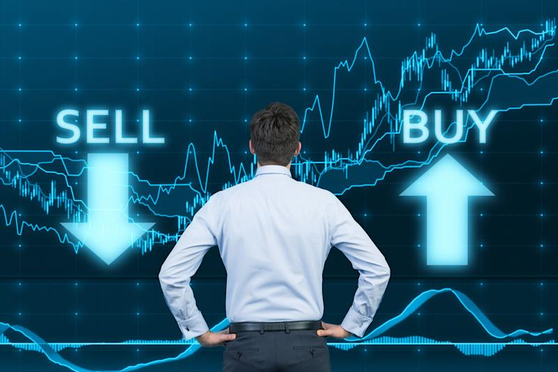 """A businessman looking at a stock price chart with the words """"buy"""" and """"sell"""" on it."""