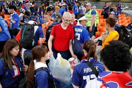 Soccer Football - World Cup - Group H - Japan vs Senegal - Ekaterinburg Arena, Yekaterinburg, Russia - June 24, 2018 Japan fans and staff clean up after the match REUTERS/Carlos Garcia Rawlins