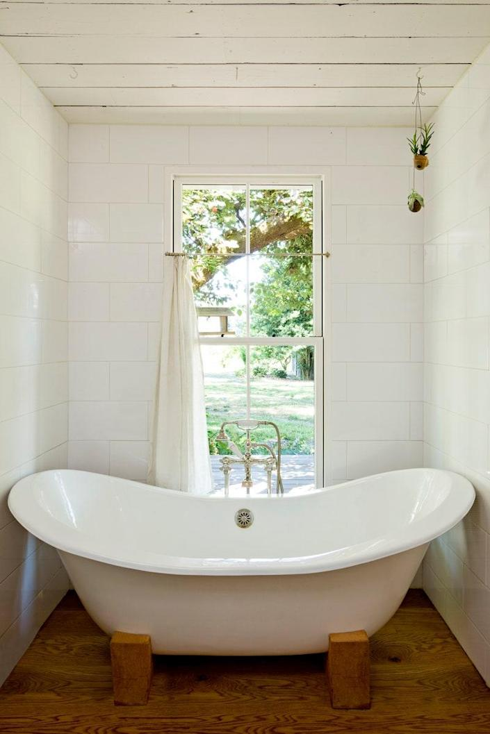 The guest tub was salvaged from a friend's home. Doulis designed and built its wooden feet to replace the original polished chrome lion feet.