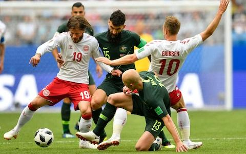 Denmark's Lasse Schone, left, and Christian Eriksen, right, are challenged by Australia's Mile Jedinak, center, and Aaron Mooy during the group C match between Denmark and Australia at the 2018 soccer World Cup in the Samara Arena in Samara, Russia, Thursday, June 21, 2018 - Credit: AP