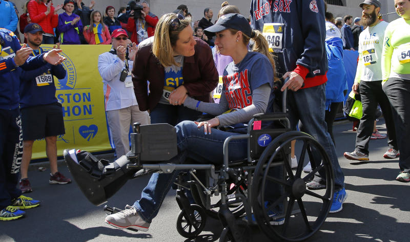 Gregory crosses the marathon's finish line in a wheelchair during a 2014 Tribute Run for survivors and first respondersin Boston.