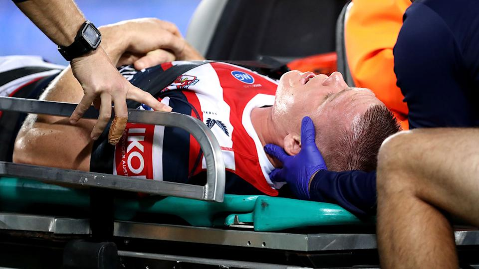 Roosters forward Lindsay Collins is stretchered off the field after a sickening head clash against the Rabbitohs. Pic: Getty