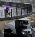 A woman walks with a dog along Brooklyn Heights Promenade while traffic travels beneath, Friday April 5, 2019, in New York. The promenade makes up the top deck overhang of a deteriorating Brooklyn-Queens Expressway and the city's plans for repairs has drawn neighborhood protest, since it calls for a temporary six lane highway on the promenade. (AP Photo/Bebeto Matthews)