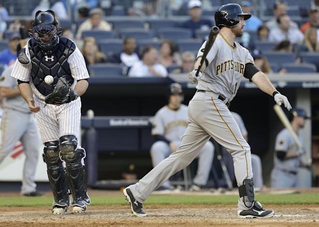 New York Yankees catcher Brian McCann, left, pops the ball out of his glove after Pittsburgh Pirates first baseman Ike Davis (15) swung and missed for strike three to end the top of the eighth inning of a baseball game, Saturday, May 17, 2014, in New York. The Yankees won 7-1. (AP Photo/Julie Jacobson)
