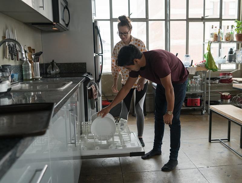 Young pregnant couple cleaning up after meal.