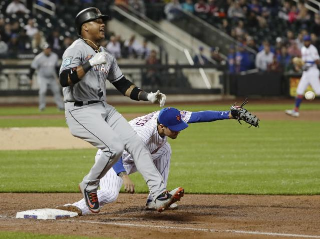 Miami Marlins' Starlin Castro (13) is safe at first base as New York Mets third baseman Wilmer Flores loses control of the ball during the fifth inning of a baseball game Tuesday, May 22, 2018, in New York. Castro advanced to second base on a throwing error by shortstop Jose Reyes. (AP Photo/Frank Franklin II)