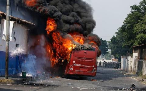 A bus that was torched during clashes with the Bolivarian National Guard burns in Urena, Venezuela - Credit: AP