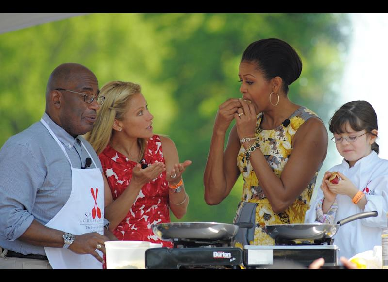 First Lady Michelle Obama samples a crepe as TV personalities Al Roker and Kelly Rippa looks on during an health eating event at the annual Easter egg roll April 25, 2011 on the South Lawn of the White House in Washington, DC. AFP PHOTO/Mandel NGAN (Photo credit should read MANDEL NGAN/AFP/Getty Images)