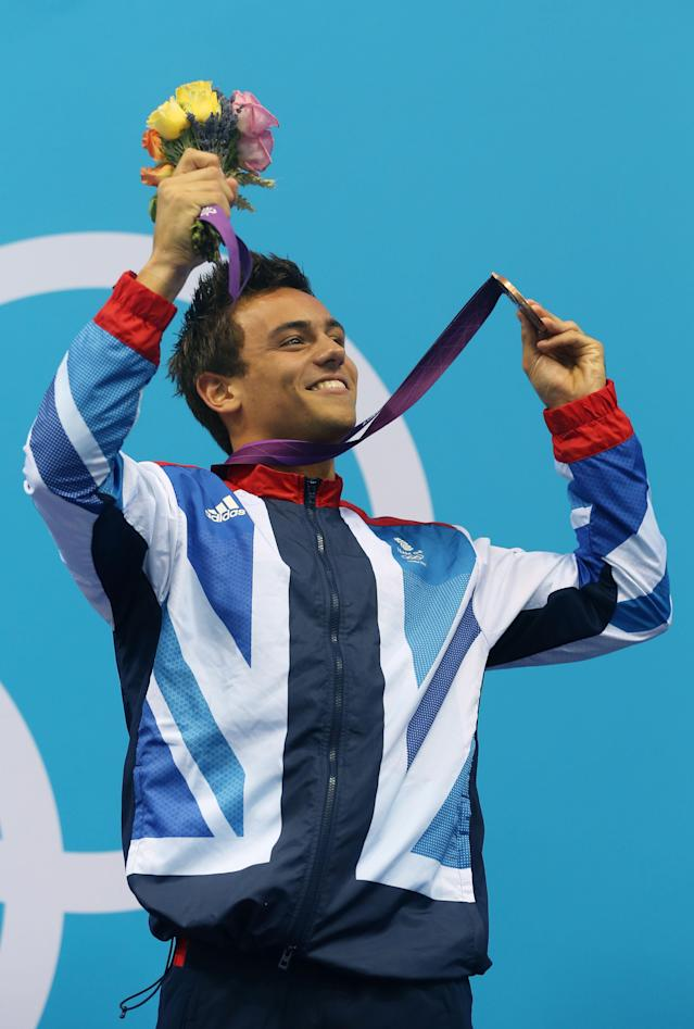 LONDON, ENGLAND - AUGUST 11: Bronze medallist Tom Daley of Great Britain celebrates on the podium during the medal ceremony for the Men's 10m Platform Diving Semifinal on Day 15 of the London 2012 Olympic Games at the Aquatics Centre on August 11, 2012 in London, England. (Photo by Clive Rose/Getty Images)