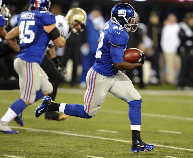 New York Giants running back David Wilson rushes past New Orleans Saints defenders to score a touchdown on a 97-yard kickoff return during the first half of an NFL football game, Sunday, Dec. 9, 2012, in East Rutherford, N.J. (AP Photo/Bill Kostroun)