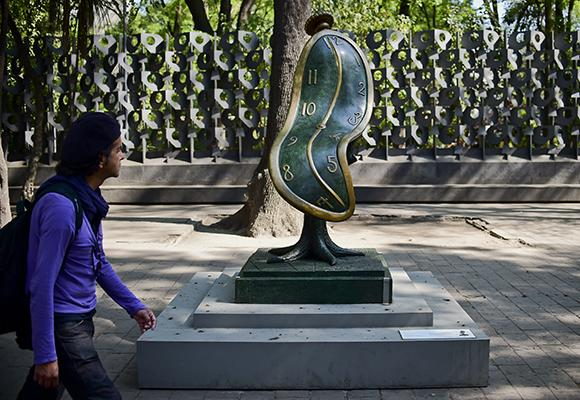 """A man looks at the """"Dance of Time I"""" sculpture by Spanish artist Salvador Dali during the exhibition """"Salvador Dali: Urban Dreams"""" along Reforma avenue, in Mexico City, on March 14, 2017."""
