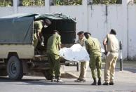 Tanzanian security forces remove the slain body of an attacker who was wielding an assault rifle, outside the French embassy in the Salenda area of Dar es Salaam