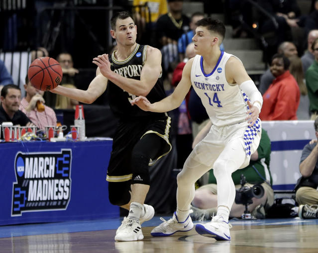 <p>Wofford's Fletcher Magee, left, passes the ball around Kentucky's Tyler Herro (14) during the first half of a second-round game in the NCAA men's college basketball tournament in Jacksonville, Fla., Saturday, March 23, 2019. (AP Photo/John Raoux) </p>