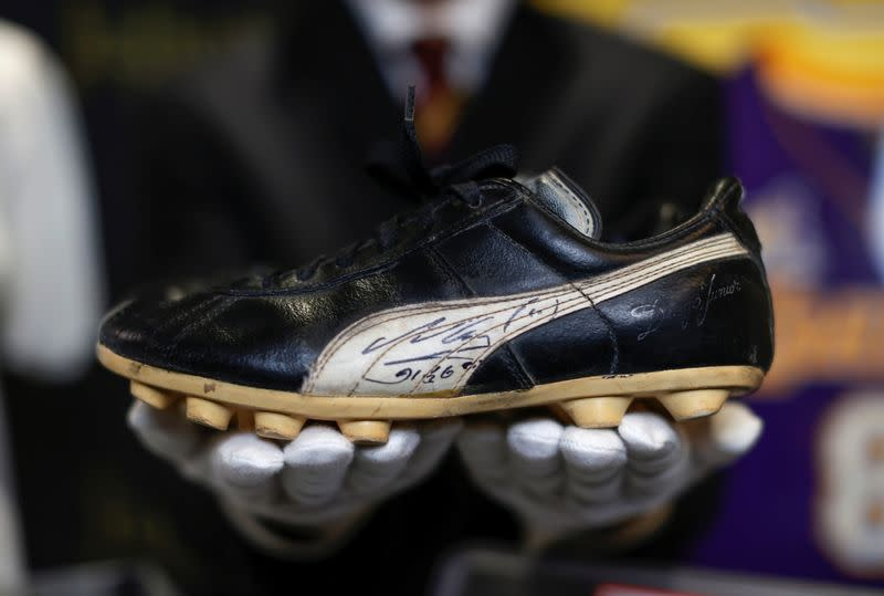 "Kendall Capps holds a pair of soccer boots worn and autographed by late soccer star Diego Armando Maradona ahead of the upcoming ""Sports: Legends"" auction in Culver City"