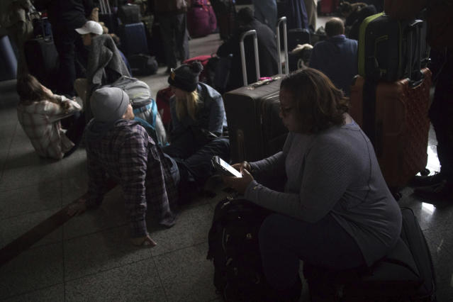 Passengers wait for the lights to come back on at Hartsfield-Jackson Atlanta International Airport Sunday, Dec. 17, 2017. A power outage at the airport disrupted ingoing and outgoing flights for hours. (Steve Schaefer/Atlanta Journal-Constitution via AP)