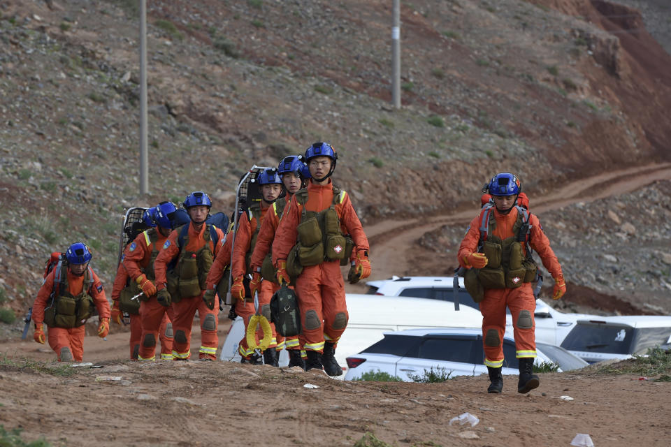 In this photo provided by China's Xinhua News Agency, rescuers walk into the accident site to search for survivors in Jingtai County of Baiyin City.