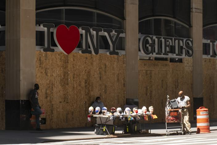 Vendors sell masks outside of a boarded up store in Times Square.