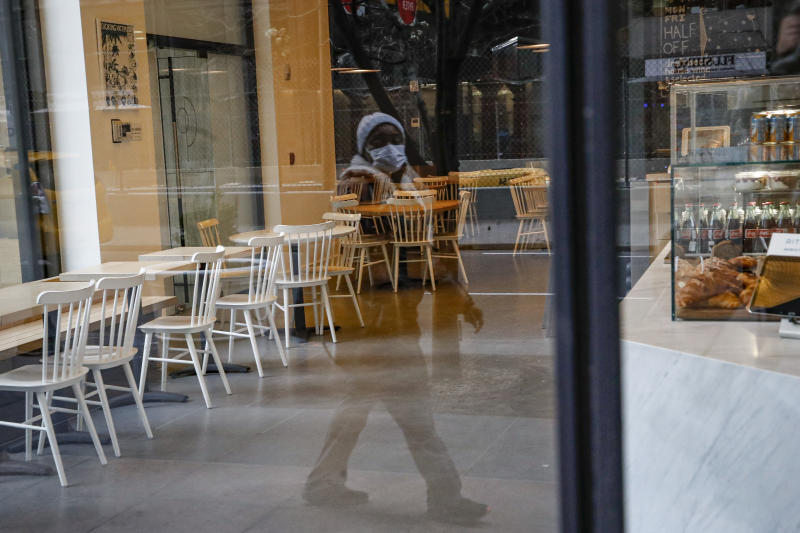 A pedestrian wearing a protective face mask walks past a nearly empty restaurant near Grand Central Terminal, Monday, March 16, 2020, in New York. New York leaders took a series of unprecedented steps Sunday to slow the spread of the coronavirus, including canceling schools and extinguishing most nightlife in New York City. (AP Photo/John Minchillo)