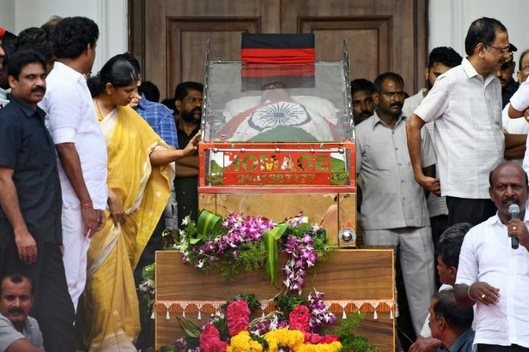 Indian MP Kannimozhi of the DMK party looks at the body of her father and DMK president Muthuvel Karunanidhi as others gather to pay respects