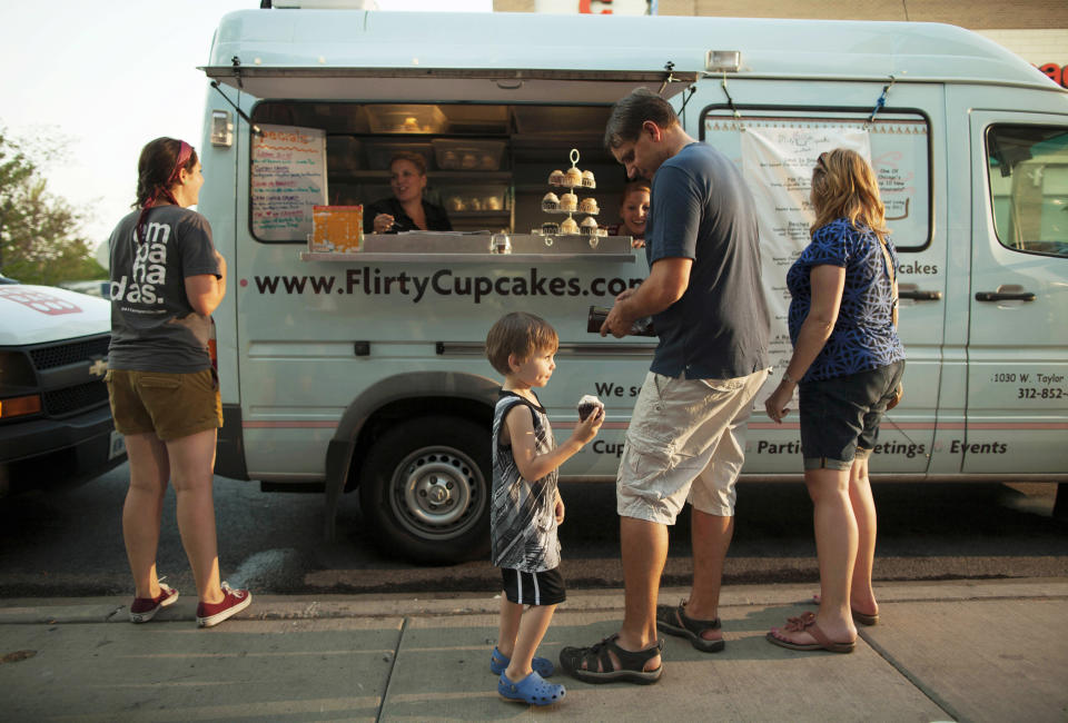 FILE - In this July 12, 2012 file photo, a young customer eats a cupcake bought from the Flirty Cupcakes food truck in Chicago. The cupcake truck's owner, Tiffany Kurtz, has also opened a bakery in Chicago called the Flirty Cupcake Dessert Garage. Food trucks have been around for generations but have flourished in a weak economy because consumers are looking for an inexpensive meal that's not just a hot dog and soda. (AP Photo/Sitthixay Ditthavong, File)