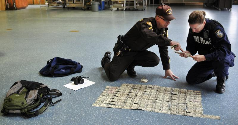 Somerset County Sheriff's Office Cpl. Gene Cole, left, helps Maine State Police Trooper Diane Vance inventory money recovered from Christopher Knight Tuesday April 9, 2013 at the Pine Tree Camp in Rome. Knight, a hermit who lived in the woods since April 1986, was apprehended when he broke into the camp, police claim. He was captured carrying a knapsack and bag of tools. Many of bills date from the 1980s and 1990s, Vance said, and were never circulated by Knight. (Photo by Andy Molloy/Portland Press Herald via Getty Images)