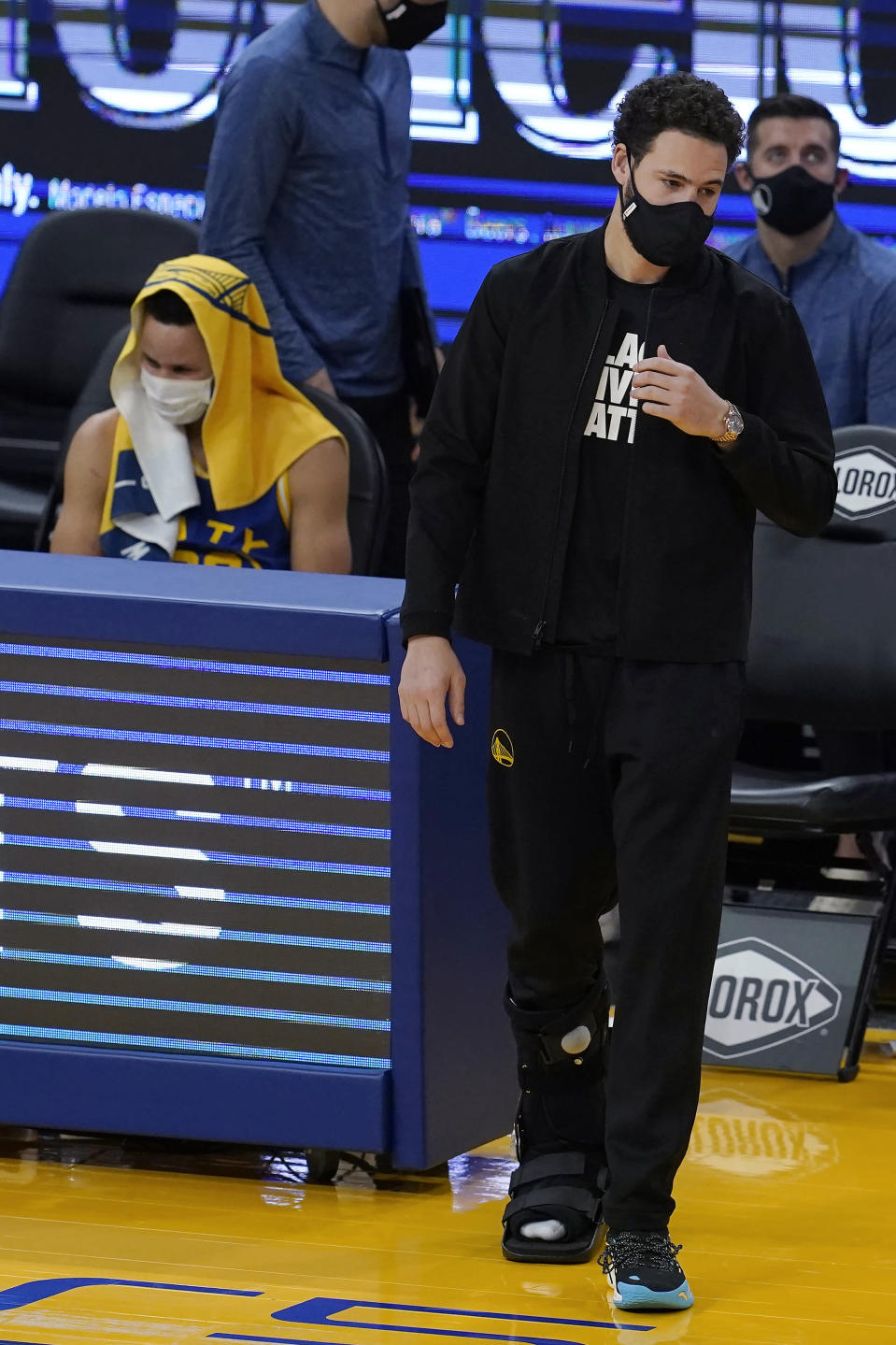 Injured Golden State Warriors guard Klay Thompson, right, walks next to guard Stephen Curry during the first half of the team's NBA basketball game against the New York Knicks in San Francisco, Thursday, Jan. 21, 2021. (AP Photo/Jeff Chiu)