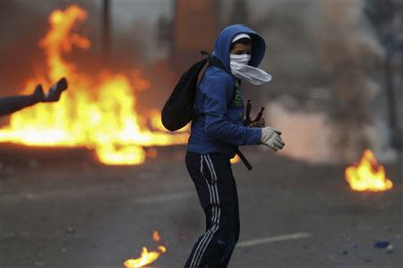 An anti-government protester turns after throwing a molotov at police during clashes in Caracas March 15, 2014. REUTERS/Jorge Silva