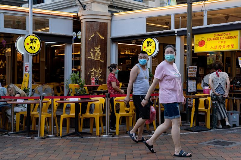 People wearing masks walk on the street in Chinatown on 15 March, 2020, in Singapore. (PHOTO: Getty Images)