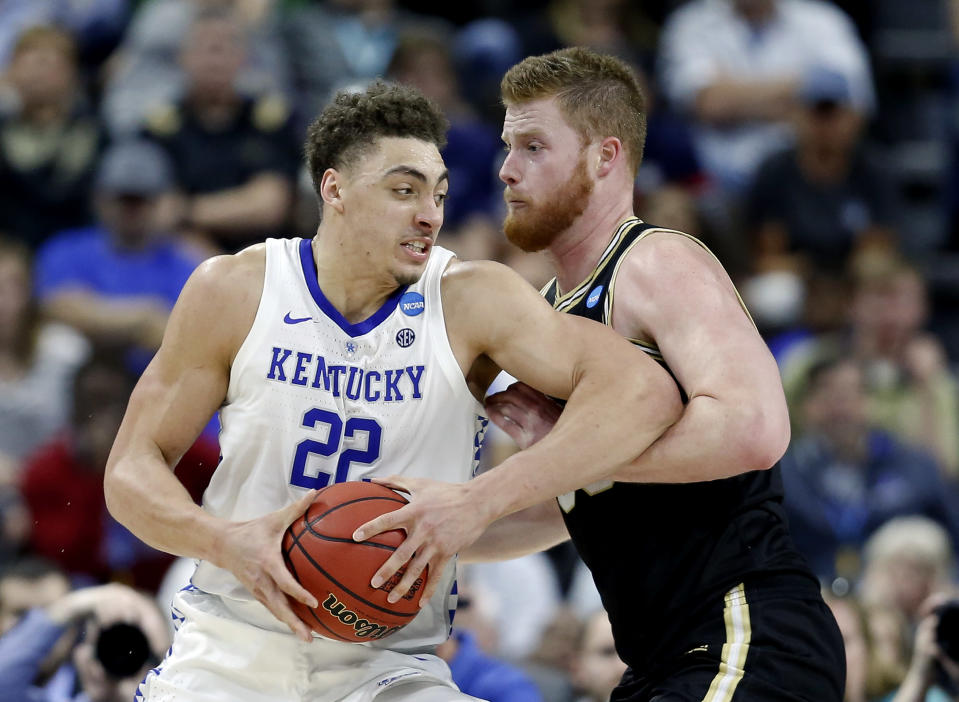 <p>Kentucky's Reid Travis (22) goes in for a shot against Wofford's Matthew Pegram during the first half of a second-round game in the NCAA men's college basketball tournament in Jacksonville, Fla., Saturday, March 23, 2019. (AP Photo/Stephen B. Morton) </p>