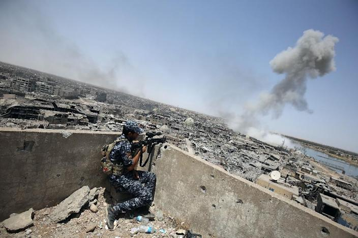 An Iraqi forces sniper looks on as smoke billows, following an air strike by US-led international coalition forces targeting the Islamic State (IS) group in the Old City of Mosul on July 9, 2017 (AFP Photo/Ahmad al-Rubaye)