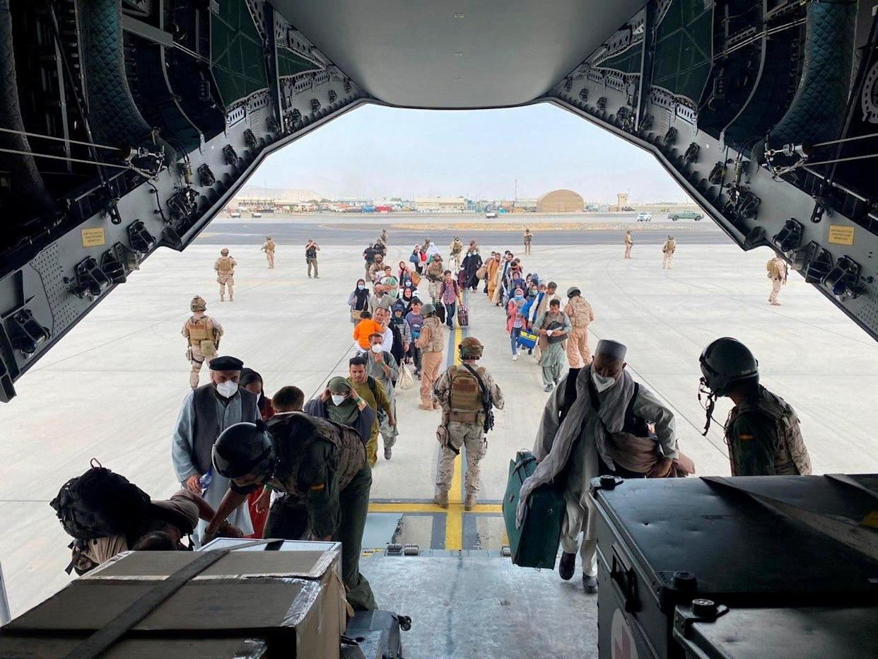 Afghans and Spanish citizens residing in Afghanistan board a military plane as part of their evacuation, at the Hamid Karzai International Airport in Kabul, Afghanistan, August 18, 2021. (Ministry of Defense of Spain/Handout via Reuters)
