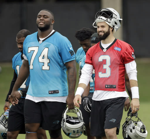 Carolina Panthers players Greg Little (74) and Will Grier (3) leave the field after the NFL football team's rookie camp practice Charlotte, N.C., Saturday, May 11, 2019. (AP Photo/Chuck Burton)