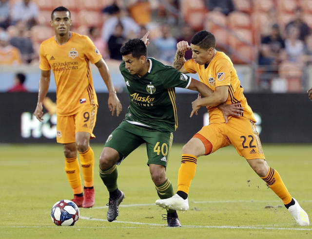 Portland Timbers midfielder Renzo Zambrano (40) moves the ball between Houston Dynamo forward Mauro Manotas (9) and midfielder Matias Vera (22) during the first half of an MLS soccer match Wednesday, May 15, 2019, in Houston. (AP Photo/Michael Wyke)