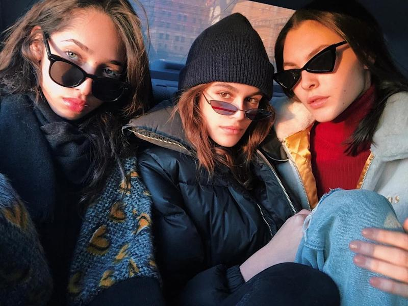 Model friends Kaia Gerber, Vittoria Cerretti and Yasmin Wijnaldum brace the winter cold fresh faced in matching black sunglasses.