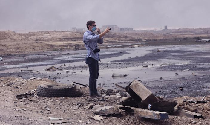 Matt Willingham of Preemptive Love Coalition stands at the Qayyarah checkpoint, where burning oil still consumes the area. (Photo: Ash Gallagher for Yahoo News)