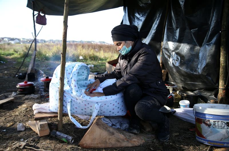 An Afghan woman tends to her seven-day-old baby at a makeshift camp near Velika Kladusa