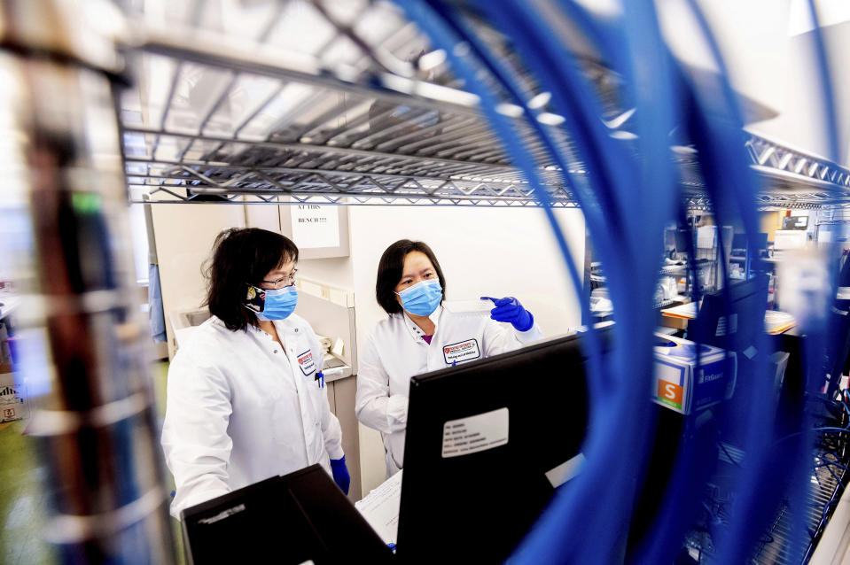 Marilyn Mar, right, and Nai-Hua Jeng process upper respiratory samples from patients suspected of having COVID-19 at the Stanford Clinical Virology Laboratory on Wednesday, Feb. 3, 2021, in Palo Alto, Calif. Viruses mutate constantly. To stay ahead of the threat, scientists analyze samples for genetic changes, watching closely for ones that might make the virus more infectious or more deadly. (AP Photo/Noah Berger)