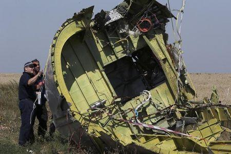 Members of a group of international experts inspect the territory at the site where the downed Malaysia Airlines flight MH17 crashed, near the village of Hrabove