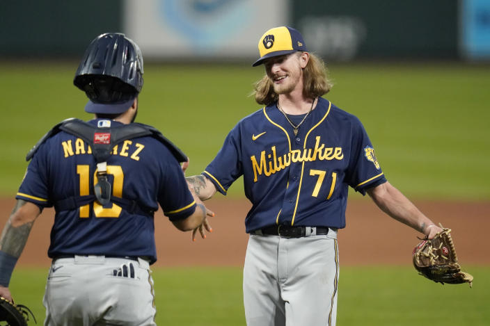 Milwaukee Brewers relief pitcher Josh Hader (71) and catcher Omar Narvaez (10) celebrate a 3-0 victory over the St. Louis Cardinals in a baseball game Saturday, Sept. 26, 2020, in St. Louis. (AP Photo/Jeff Roberson)