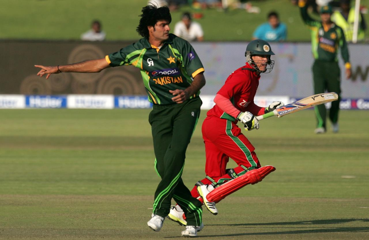 Pakistan's bowler Muhammad Irfan (L) gestures as Zimbabwe's batsman Malcolm Waller runs between wickets during the second game of the three match ODI cricket series between Pakistan and hosts Zimbabwe at the Harare Sports Club August 29, 2013.AFP PHOTO / JEKESAI NJIKIZANA        (Photo credit should read JEKESAI NJIKIZANA/AFP/Getty Images)