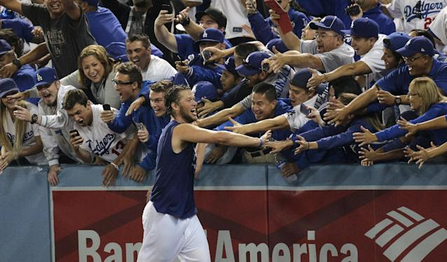 Los Angeles Dodgers starting pitcher Clayton Kershaw celebrates with fans after the Dodgers defeated the Atlanta Braves 4-3 in Game 4 of the National League baseball division series and advanced to the NL championship series, Monday, Oct. 7, 2013, in Los Angeles. (AP Photo/Jae C. Hong)