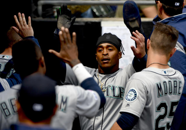 Seattle Mariners' Mallex Smith, center, celebrates in the dugout after scoring against the Chicago White Sox during the third inning of a baseball game in Chicago, Saturday, April 6, 2019. (AP Photo/Matt Marton)