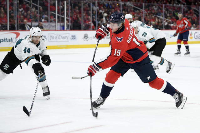 Washington Capitals center Nicklas Backstrom (19), of Sweden, shoots the puck next to San Jose Sharks defenseman Marc-Edouard Vlasic (44) during the second period of an NHL hockey game, Sunday, Jan. 5, 2020, in Washington. (AP Photo/Nick Wass)