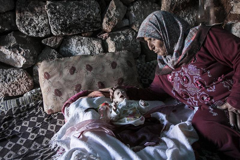 In this Friday, Sept. 27, 2013 photo, a displaced Syrian woman comforts her one-month old grandchild Fatima inside a stone house near Kafer Rouma, in ancient ruins used as temporary shelter by those families who have fled from the heavy fighting and shelling in the Idlib province countryside of Syria. Fatima was born just a month ago amid the ancient ruins outside Kafer Rouma, a village in northern Syria that has come under shelling by President Bashar Assad's forces during the country's civil war. Her family fled their home in the village to the giant stone blocks and centuries-old walls so that Fatima's mother could give birth in relative safety.(AP Photo)