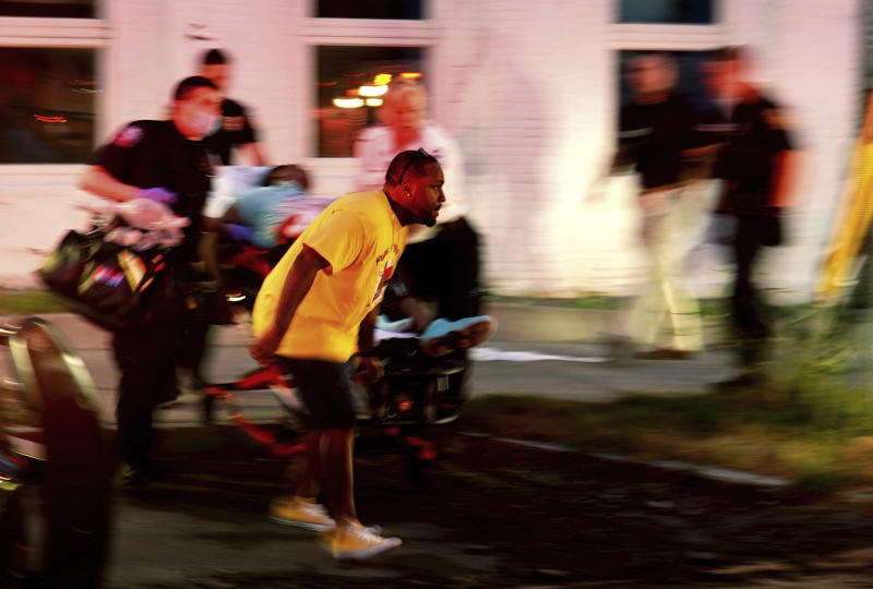 Emergency response crews move wounded people to ambulances after multiple people were shot at a party Saturday, June 20, 2020, in Syracuse, N.Y. Nine people were shot and one victim, a 17-year-old boy, was in critical condition Sunday. (Ellen M. Blalock/Syracuse Post-Standard via AP)