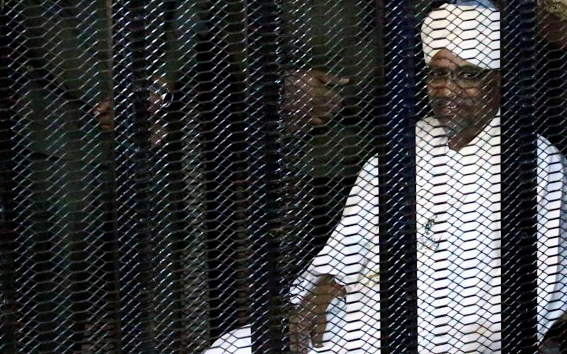 Omar al-Bashir sat in a metal cage at the opening of his corruption trial - REUTERS
