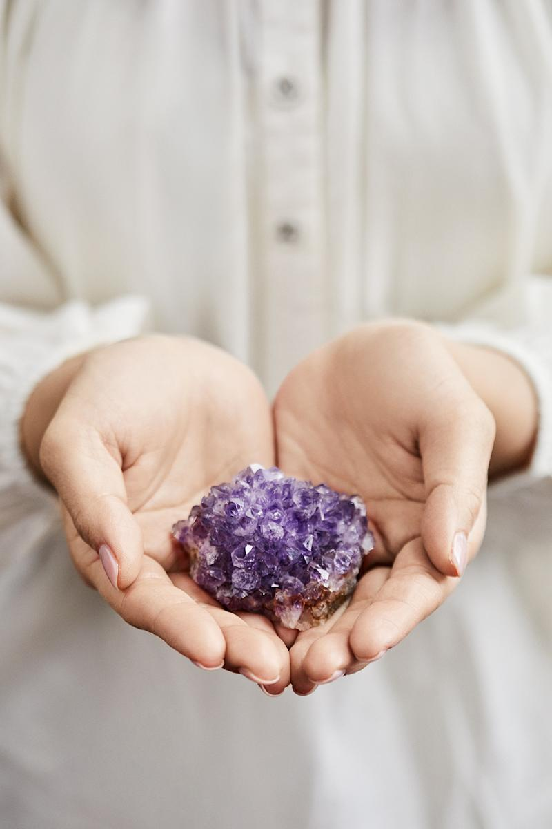holding purple crystals in hands