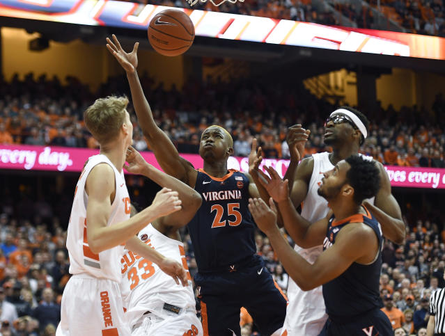 Virginia forward Mamadi Diakite (25) reaches for a rebound during the first half of an NCAA college basketball game against Syracuse in Syracuse, N.Y., Monday, March 4, 2019. (AP Photo/Adrian Kraus)