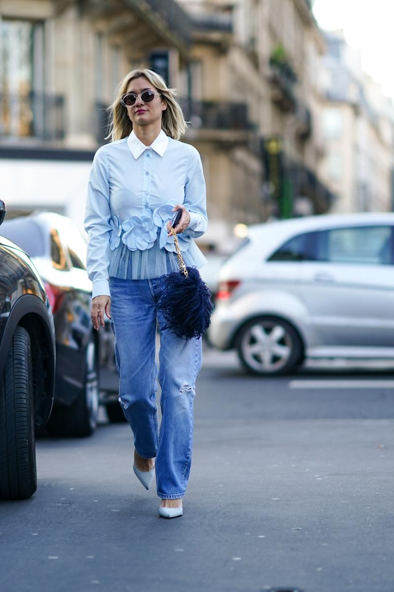 PARIS, FRANCE - JANUARY 22: Anne-Laure Mais wears sunglasses, a light blue ruffled shirt with a white collar and flowers embroidered, blue ripped jeans, light blue pointy pumps, a bag decorated with navy-blue feathers, outside Viktor & Rolf, during Paris Fashion Week - Haute Couture Spring/Summer 2020, on January 22, 2020 in Paris, France. (Photo by Edward Berthelot/Getty Images )