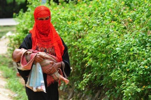 """A Rohingya Muslim woman walks with her child at an unregistered refugee camp in Teknaf, Bangladesh, on June 20, 2012. Myanmar's president Thursday told the UN that refugee camps or deportation was the """"solution"""" for nearly a million Rohingya Muslims in the wake of communal unrest in the west of the country"""